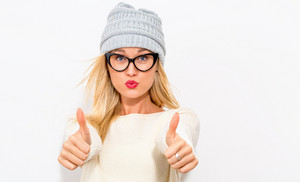 Happy young woman giving thumbs up on a white background