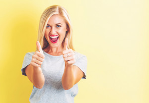 Happy young woman giving thumbs up on a yellow background
