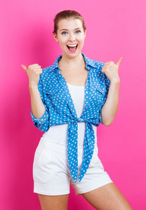 Happy young woman giving thumbs up on pink background