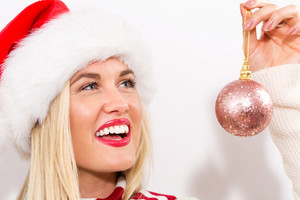 Happy young woman holding a Christmas bauble
