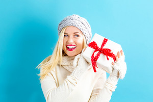 Happy young woman holding a Christmas present box