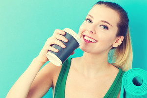 Happy young woman holding a coffee cup and a yoga mat