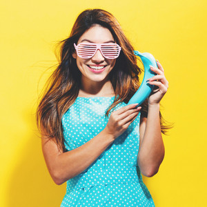 Happy young woman holding a colored banana on a yellow background