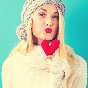 Happy young woman holding a heart cushion on a blue background
