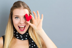 Happy young woman holding a heart cushion on a gray background