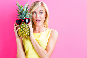 Happy young woman holding a pineapple on a pink background