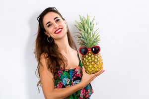 Happy young woman holding a pineapple on a white background