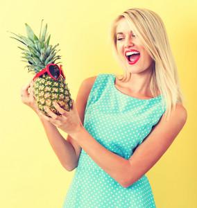 Feliz mulher jovem segurando um abacaxi em um fundo amarelo