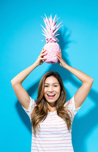 Happy young woman holding a pineapple on blue background