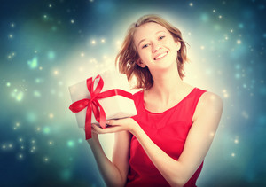 Happy young woman holding a present box in snowy night