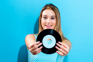 Happy young woman holding a record on a blue background