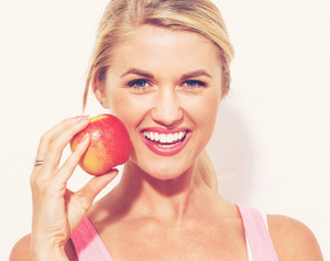 Happy young woman holding a red apple