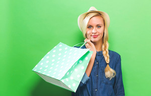 Happy young woman holding a shopping bag on a green background