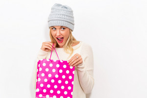 Happy young woman holding a shopping bag on a white background