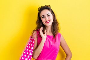 Happy young woman holding a shopping bag on a yellow background