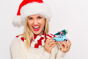 Happy young woman holding a small car with Christmas tree