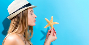 Happy young woman holding a starfish on a blue background