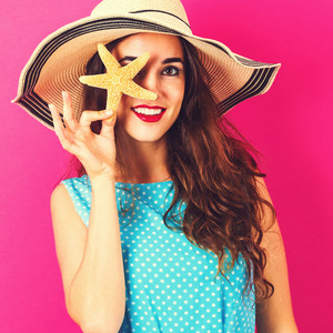 Happy young woman holding a starfish on a pink background