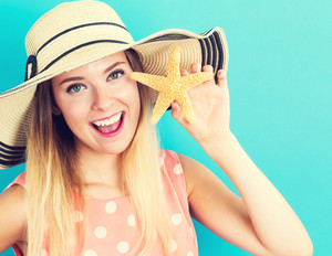 Happy young woman holding a starfish on blue background