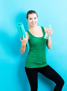 Happy young woman holding a yoga mat and a water bottle
