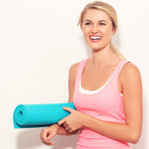 Happy young woman holding a yoga mat