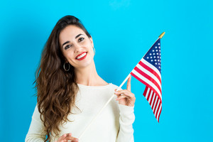 Happy young woman holding American flag on a blue Background