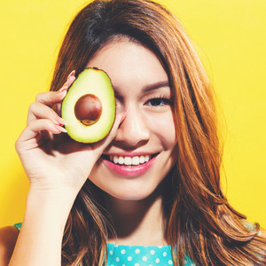Happy young woman holding an avocado halve on a yellow background