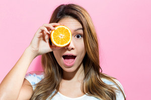 Happy young woman holding an orange on a pink background