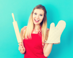 Happy young woman holding an oven mitt and a rolling pin