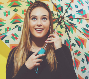 Happy young woman holding an umbrella on a yellow background
