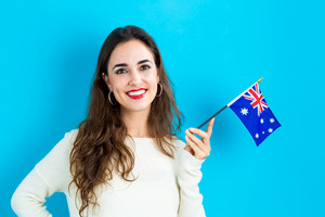 Happy young woman holding Australian flag on a blue Background