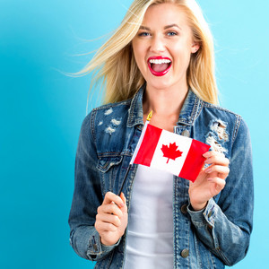 Happy young woman holding Canadian flag on a blue background