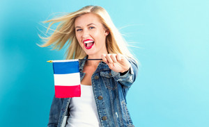 Happy young woman holding French flag on a blue background