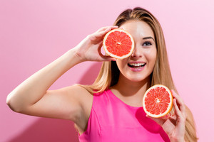 Happy young woman holding grapefruit halves on a pink background