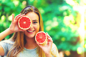 Happy young woman holding grapefruit halves outside