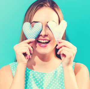 Happy young woman holding heart cushions on a blue background