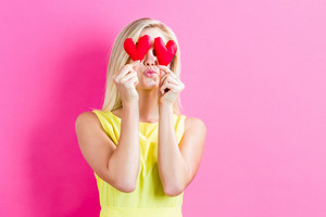 Happy young woman holding heart cushions on a pink background
