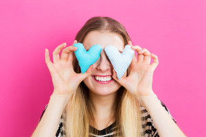 Happy young woman holding heart cushions on pink background