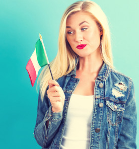 Happy young woman holding Italian flag on a blue background