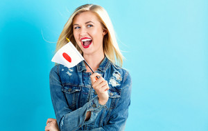 Happy young woman holding Japanese flag on a blue background
