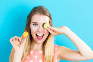 Happy young woman holding macarons on a blue background