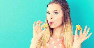 Happy young woman holding macarons on blue background