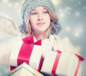 Happy young woman holding many gift boxes in snowy night