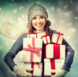 Happy young woman holding many present boxes in snowy night