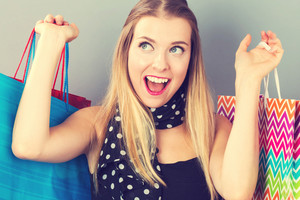 Happy young woman holding many shopping bags on a gray background