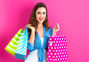 Happy young woman holding many shopping bags on a pink background
