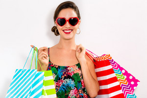 Happy young woman holding many shopping bags on a white background