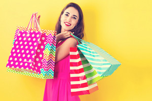 Happy young woman holding many shopping bags on a yellow background