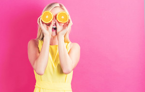 Happy young woman holding oranges halves on a pink background
