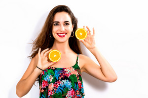 Happy young woman holding oranges halves on a white background
